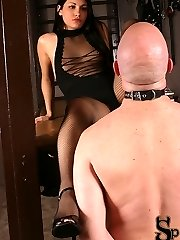 Jade exposes that she is a Domina by night. Clad in a stellar sheer outfit with fishnet stockings, she puts a band on him before he starts to kiss her feet. She makes him gargle on the heel of her stiletto and shoves it in and out of his mouth.