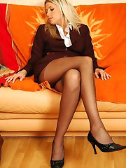 Awesome business woman relaxing while tenderly massaging her nyloned feet