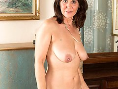 Busty mature babe Kaysy spreads trimmed pussy.