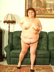 Mature redhead BBW totally naked and spreading her fat thighs wide to examine her wet pussy