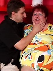 Naughty mature Margaret spread legged on the bed while a spunk-pump pounds her fat snatch