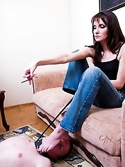 Lounging at her feet, the stud serves his lady for a carpet, a foot licker and an ash-stand