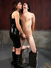 Miss Olive isn't convinced that her slave, perverted kade, is happy to watch her. So she decides to remind him why he should be genuinely happy to be in her presence.  She has him kneel on two cinder blocks as she smacks his cock and ball-sac.  She has him extend his cock out in front of his body with two fingers as she canes the prick of his trouser snake.  THen she uses a perforated paddle to beat on his nipple rings and frosts his balls and fuckpole with clover clamps.
