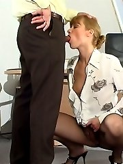 Lascivious secretary squeezing guys head with her slender pantyhosed legs