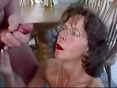 Mature black-haired in glasses fosters huge facial cumshot.