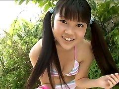 Cute Korean school schoolgirl poses in bikini in the garden