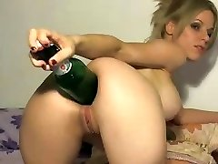 Crazy blonde uses the big end of a bottle to stick in her arse