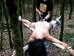 Tied to a cross and pounded with a big faux-cock in the forest