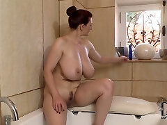 Well stacked brunette milf faux-cock fucks her cleavage in the bathtub room