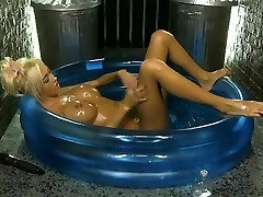 Kerrie Lee in a paddling pool covered in grease