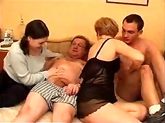 Mature couple with young couple in bed