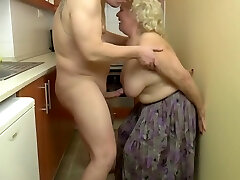 Insatiable, blonde granny is playing with her milk cans and her lovers dick, in the kitchen