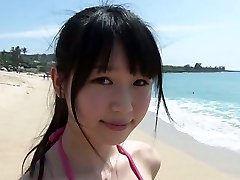 Slim Chinese girl Tsukasa Arai ambles on a sandy beach under the sun