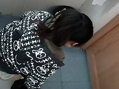 an Asian girl in a jumper pissing in public restroom for absolute ages