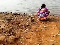 Indian woman peeing in the mud by a lake