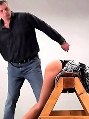 He bends her over, a rubber paddle waiting for bare smooth ass. He brings it down hard on her...