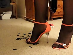 Cathy destroying toy bugs in orange heels and black tights