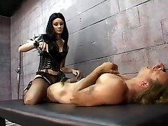Brunette mistress in corset Leah Wilde tortures a prisoner