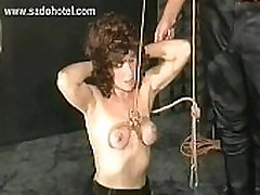 Hot slave stuck in a dungeon gets rope around her beautiful tits by two masters