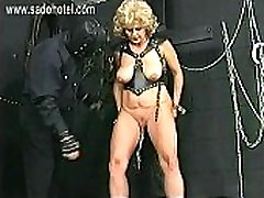 Master is spanking older slave with big tits on her ass and puts large metal clamps on her pussy
