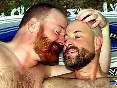 Steve Ellis is a Ginger Bear and a peeping tom. His neighbor, Andrew Mason, is definitely the type that likes to be watched and the backdoor advances are more than welcome. Each has waited far too long to lick the sweat off each other and the time is right. In the HOT summer heat, Steve and Andrew flip back and forth, drilling each other on the grass until they nearly drown in a pool of their own sweat and cum all over their furry bellies. Yummm!...