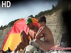 Russian nudist babe and her boyfriend sunbathe on beach