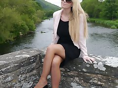 Gorgeous blonde Larissa poses by the river in a sexy black dress and matching high stiletto heels