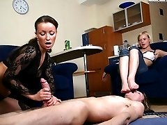 Eager slave licks his mistress�s toes while getting a nice handjob from her raunchy blonde kitty friend