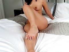 Hot brunette, Faye is naked on the bed showing off her pedicured feet!