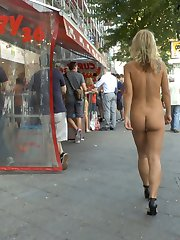 Busty blonde Luci is put on display in front of eager tourists. A group forms to watch her publicly shamed until the cops show up. Mona brings the dirty slut to a famous sausage stand where she's fully nude in front of a huge crowd. She has to stand and wait while tons of people gawk and stare. The next stop is a crowded cafe where she is tied up, blindfolded, and groped by complete strangers. After she is fed cocks and pounded in her ass and pussy, Mona gives her a final task. With a toilet brush strapped to her face, she has to clean a filthy urinal while getting cum on all over her face.