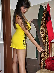 Hot dark-haired bombshell trying on several pairs of extra shiny pantyhose