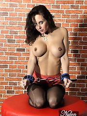 Busty brunette Helen is posing topless in a pair of red silk panties and sexy nylon stockings