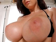 Thick brunette in a bikini pops out her massive tits