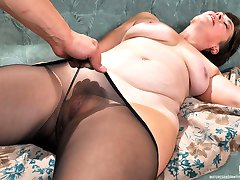 Gorgeous mommy in black tights gives a nylon legjob to a horny muscle stud