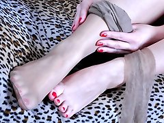Inviting stunner flashes her red toenails before putting her nylons and high-heeled slippers