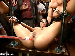 Evi Fox is a flirtatious little lady who loves to be the center of attention. She gets dragged into a bar filled with an eager crowd who are ready to get down.  Cuties from the crowd tease and torment her natural tits with clothes pins while a cock pounds her throat.  She is helpless against the hitachi that never leaves her slutty clit. It is good to see her squirm.Next She gets pinned down in metal and hand cuffs to expose her whorish pussy while she is fucked hard, flogged and cattle-prodded.  An audience member pounds her cunt with a dick on a stick and she simply cannot escape the torment of the hitachi.