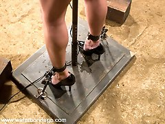 One of our favorite bondage heroines is back for another round of hot, wet fun. Wenona is ordered to fuck herself near the beginning of scene one. While already in neck/wrist stocks and high heels, Wenona rises to the occasion.  In scene 2, her mental resolve is tested in a well planned predicament bondage spread-eagle. Wet Dreams enters scene 3 while Wenona is totally screwed....down.  After some self-bondage, negative gravity nipple weights are used against her during scene 4 in the Houdini tank.  We love you Wenona!