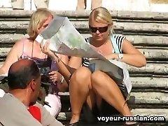 Tanned long-legged girlin a white dress thoroughly filmed on an upskirt video