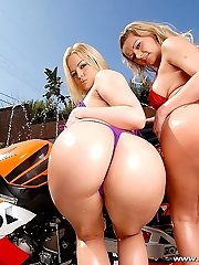 Two sexy chicks show off their big round asses in a threeway