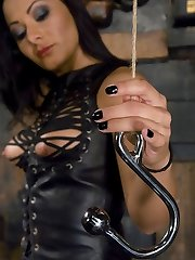 Mistress Sandra Romain taunts Lefty while he suffers in torturous predicament with his stiff cock tied to a wall and a hook up his ass pulling in the opposite direction.When the anguish becomes too much, he is bent over and ravaged up the ass to de-robe his manhood, and ultimately his salami is used and drained for Domina' sensation.