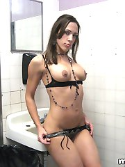 Dirty bitch Nicoletta L wears only lingerie under coat and poses in public toilet