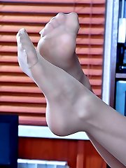 Stunning office babe dangles her stiletto pump and teases with nyloned feet