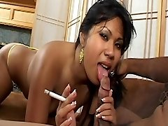 Asian honey with ultra-cute tits smokes cigarette and gets cum facial cumshot on couch