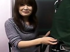 Sexy Japanese honey with a pretty grin works her hands on a