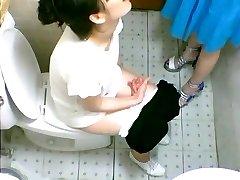 Två söta Asiatiska tjejer såg på en toalett cam pissar