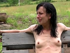 Anorexic black-haired hussy gets her slim body tied up to wooden fence outdoors