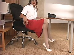 Sexy brunette in stockings and glasses spreads and toys her pussy