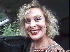 MILF con piercing en el coño y los pezones, masturbándose en el coche