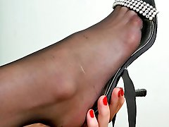Curly gal staring at her delicious feet clad in black reinforced toe tights