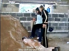 Pretty bitches trampling fat worker down into mud and sand